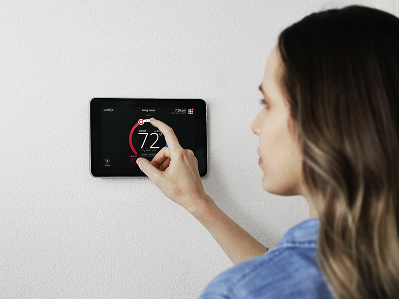 Woman adjusting smart thermostat